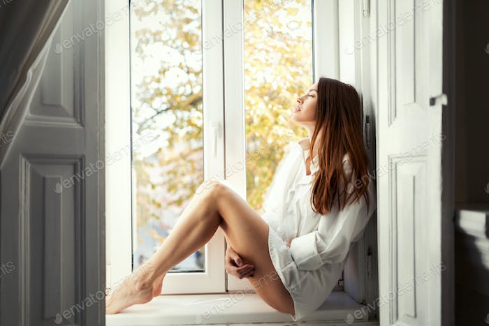 Beautiful young woman sitting by window alone