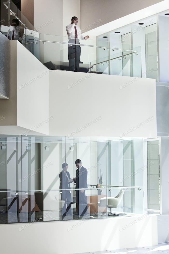 Des gens d'affaires sur deux étages d'un grand centre d'affaires.