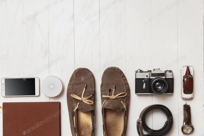 Set von Herren-Blogger-Accessoires für den Reisenden auf einem weißen Holzhintergrund.
