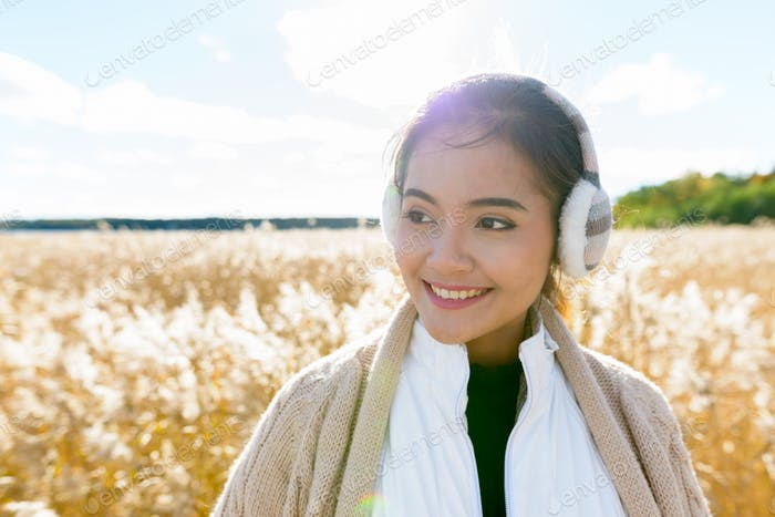 Young happy Asian woman smiling while thinking against scenic view of autumn bulrush field