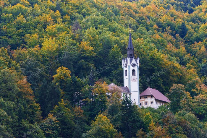 A church in a fall forest in Slovenia
