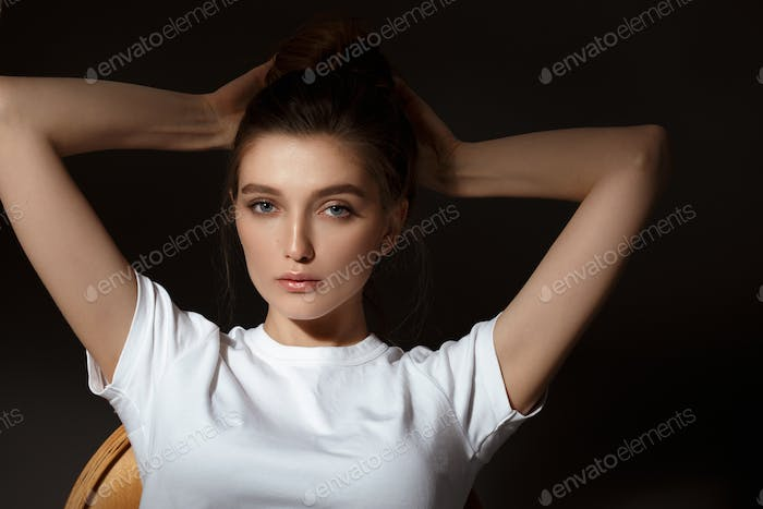 Charming brunette girl with bunched hair dressed in white t-shirt and jeans poses on the black