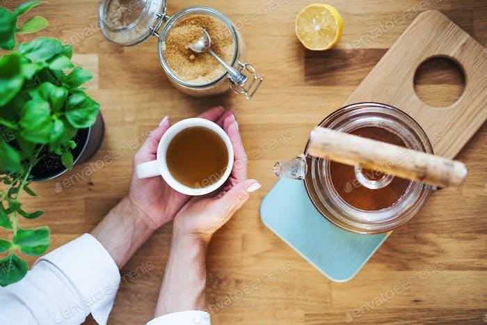 Eine Zusammensetzung der Hände halten Tasse Tee, Teekanne und Zucker auf Holztisch. Eine Draufsicht.