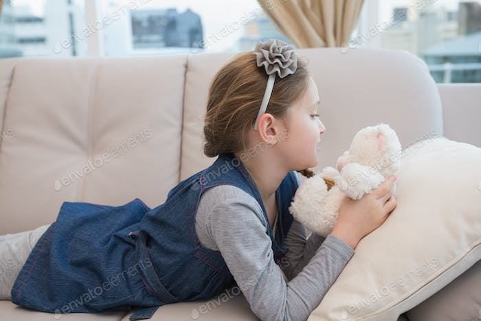 Little girl lying on the couch with teddy at home in the living room