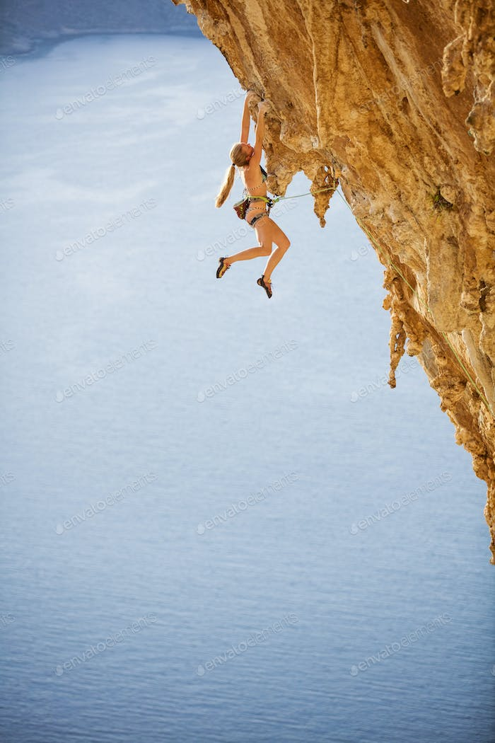 Young woman in bikini climbing challenging route over sea