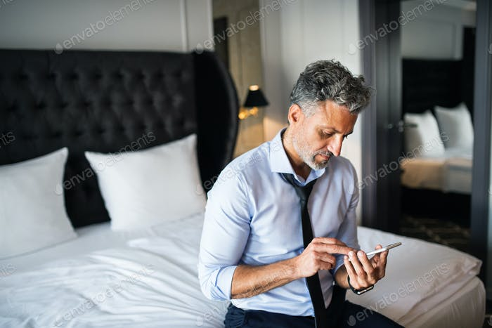 Mature businessman with smartphone in a hotel room.