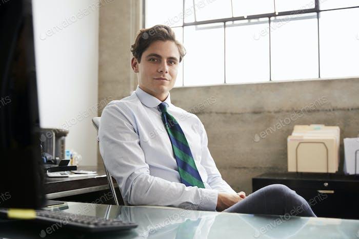Junge weiße Geschäftsmann an einem Schreibtisch suchen Kamera