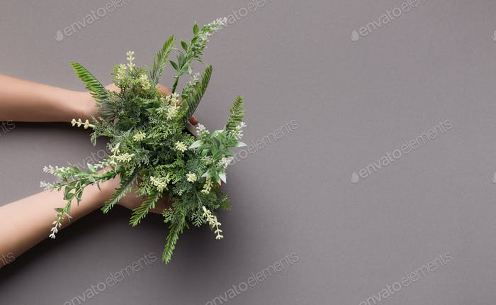 Woman holding artificial houseplant with white flowers