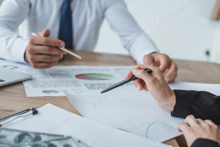 imagen recortada de asesores de negocios señalando en documentos en la mesa en la oficina