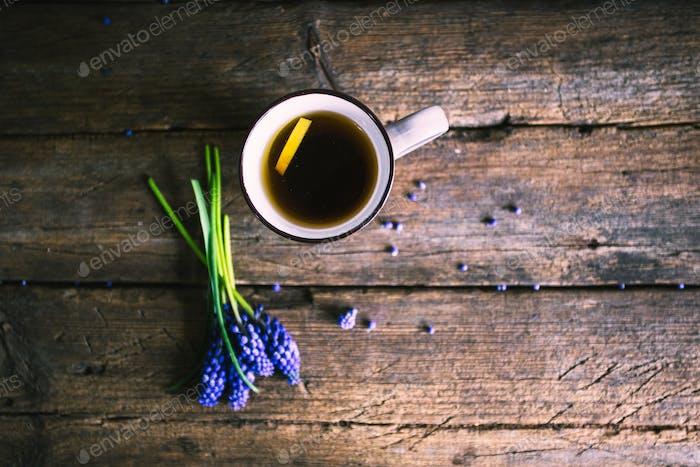 Blaue Blumen und Tasse Tee auf hölzernem Hintergrund. Vintage-Design