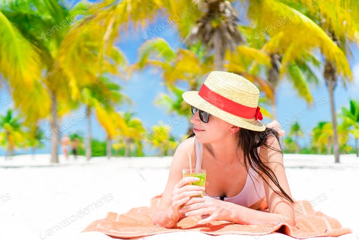 Young beautiful woman relax with cocktail on white tropical beach