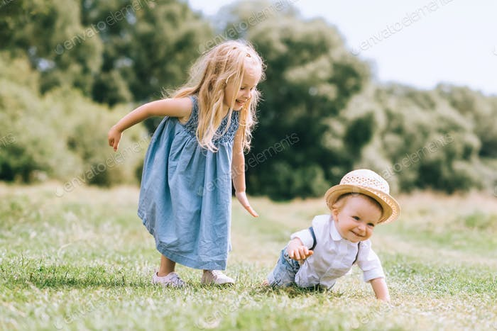 adorable blonde kids playing in field