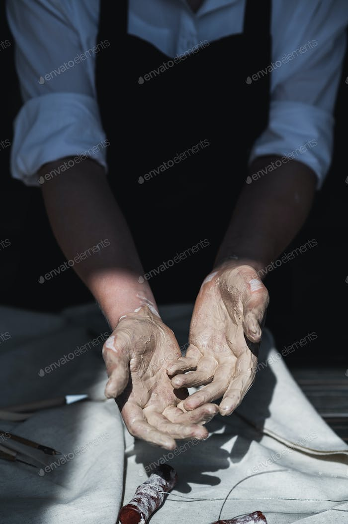 I need to wash my hands. Close up picture of female ceramic artist arms in clay after making pottery