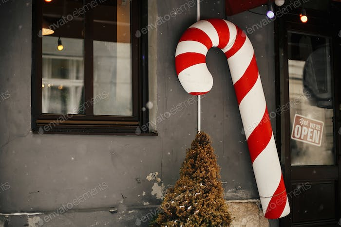 Christmas street decor. Stylish christmas big candy cane toy at store front