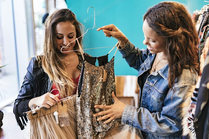 two female friends buying clothes in a store and enjoying it