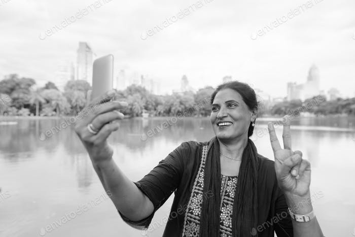 Happy mature Indian woman using phone at the park
