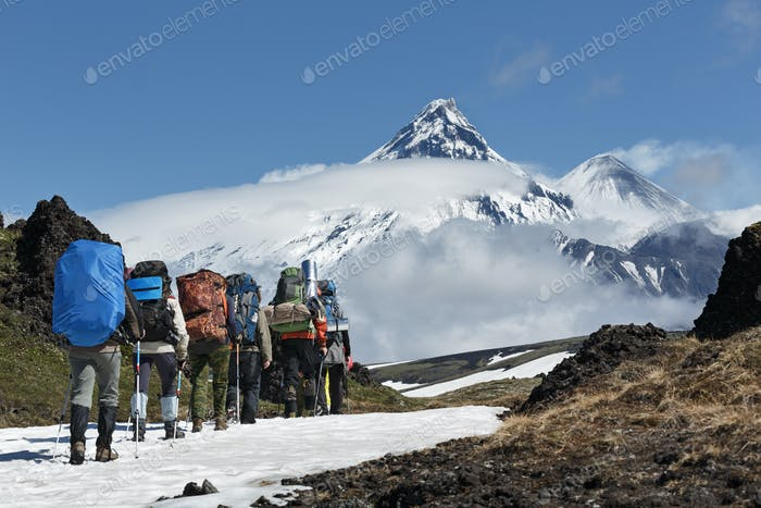 Group of Hikers Goes in Mountain on Background Volcanoes of Kamchatka Peninsula