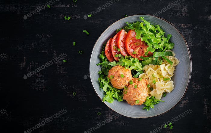 Farfalle with meatballs and salad on dark background.