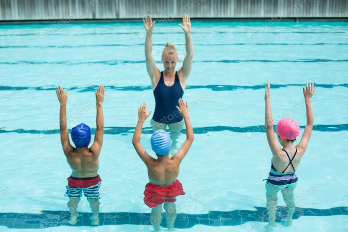 Instructor teaching students in swimming pool