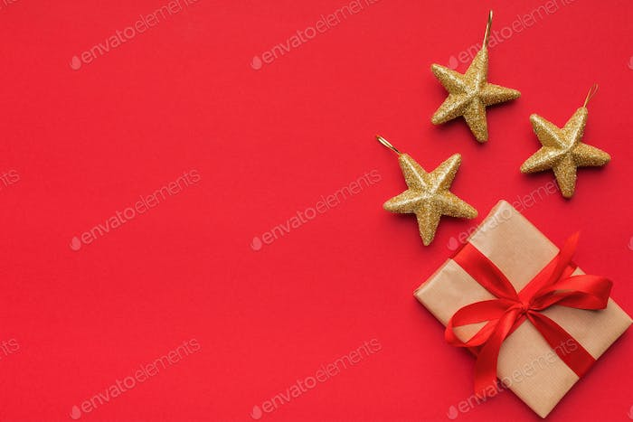Gift box with three golden stars on red background
