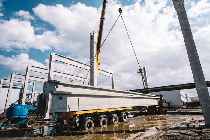 Industrial crane unloading prefabricated cement pillars from cargo