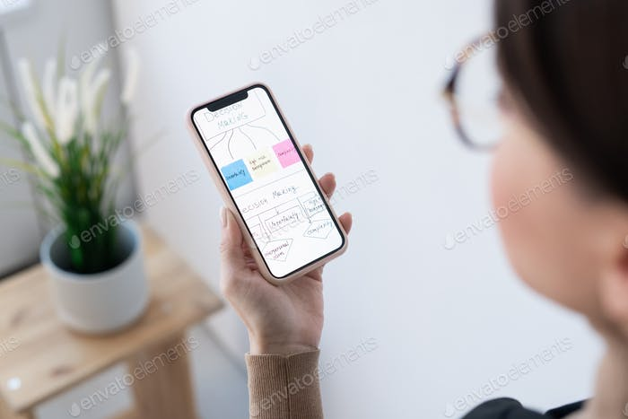 Hand of contemporary businesswoman holding smartphone with flow chart