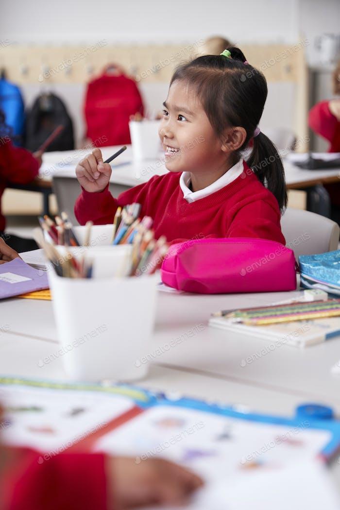 Chinesische Schulmädchen tragen Schuluniform sitzen an einem Schreibtisch in einem Klassenzimmer