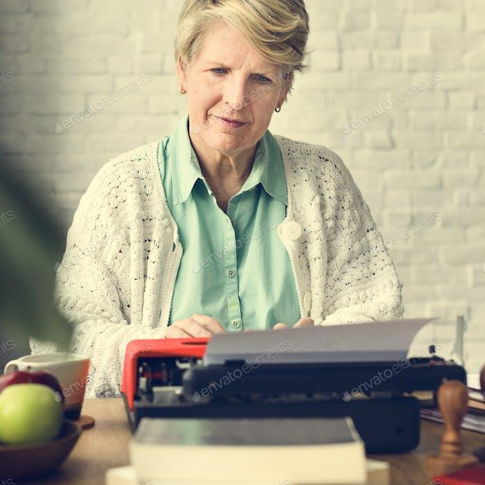 Senior Adult Using Typerwriter Typing Concept