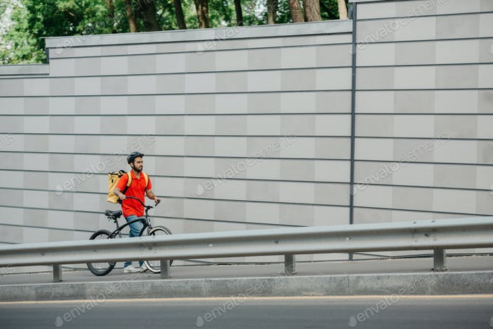 Work deliveryman in city. Courier in helmet with backpack and bicycle is tired and walking up street