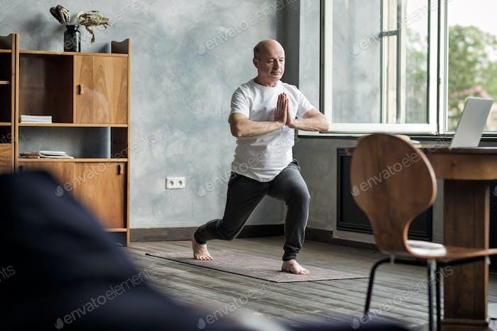 Senior hispanic man standing in warrior yoga pose variation