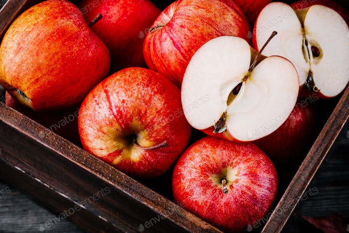red ripe apples in a box on a wooden background