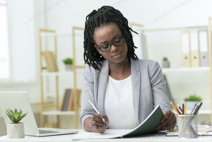 Afro Business Lady Taking Notes Working In Modern Office