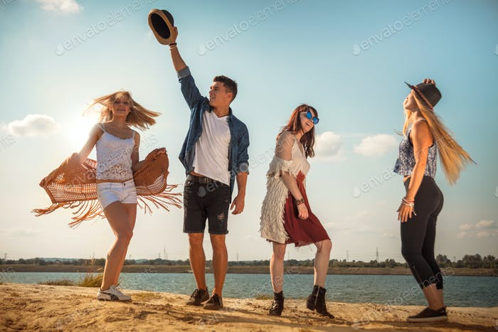Group of friends partying and dancing at the beach