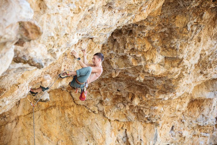 Male rock climber on a challenging route on a cliff