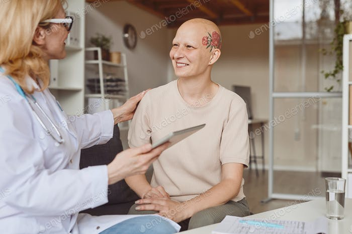 Smiling Bald Woman Talking to Female Doctor in Clinic