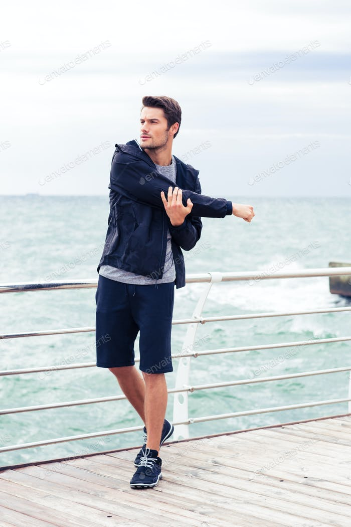Handsome sports man stretching hands outdoors