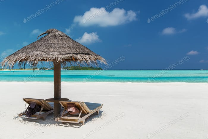 palapa and sunbeds on maldives beach