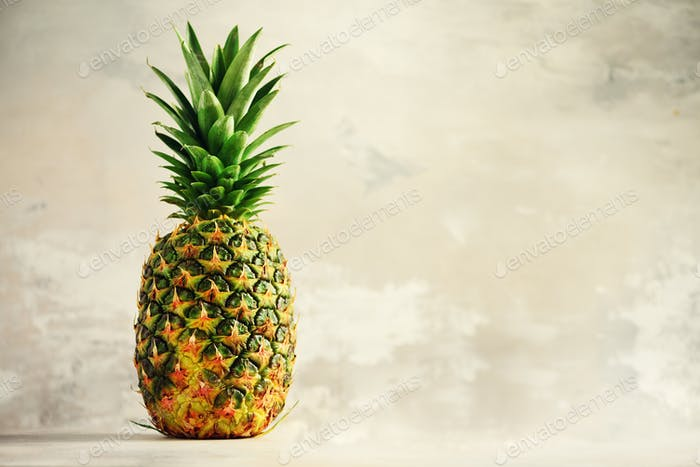 Tropical pineapples on gray background. Summer, holiday concept. Raw, vegan, vegetarian, clean