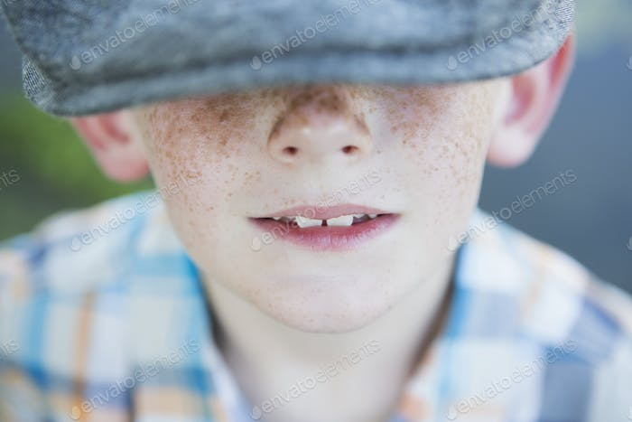 A young boy with a freckled nose, wearing a cap with a large brim.