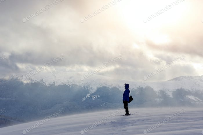 Snowshoe walker running in powder snow with beautiful sunrise light. Outdoor winter activity and