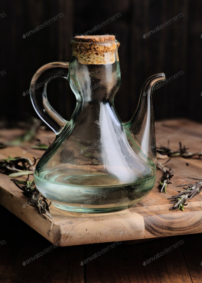 oil jugs with Spanish olive oil and branches of rosemary on rustic wood