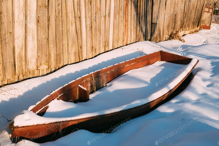 Old Wooden Abandoned Rowing Boat Covered Snow On Coast In Sunny