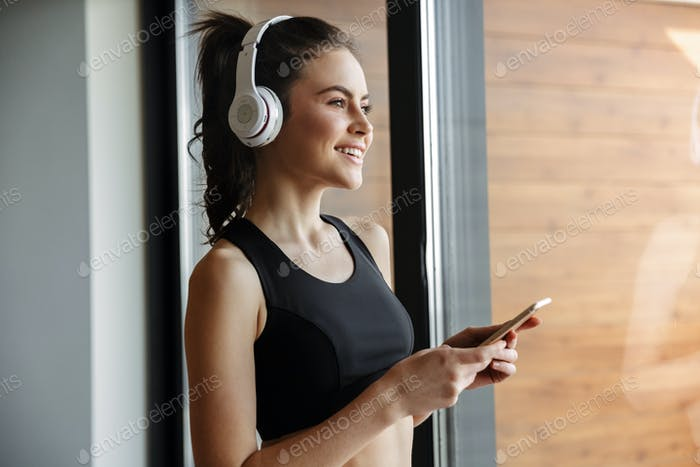 Photo of smiling seductive woman using headphones and smartphone