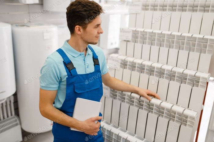 Plumber in uniform choosing water heating radiator