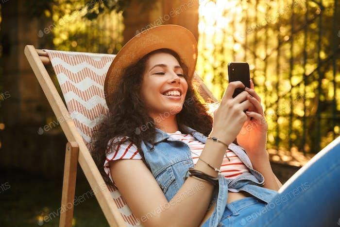 Junge schöne fröhliche lockige Frau chatten mit dem Handy.