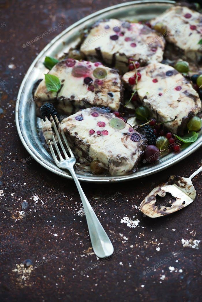 Semifreddo or italian cheese ice-cream dessert with garden berries and mint
