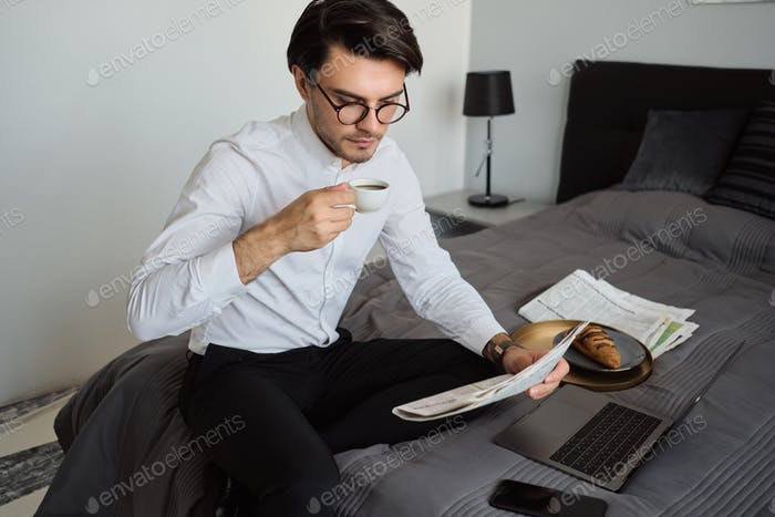 Man in shirt and eyeglasses drinking coffee thoughtfully reading newspaper sitting on bed