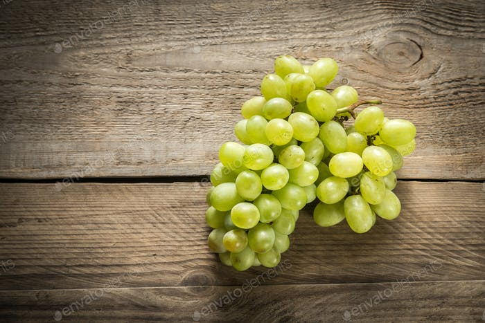 Bunch of white grape on the wooden background