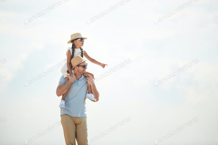 Caring Father Carrying Daughter on Shoulders