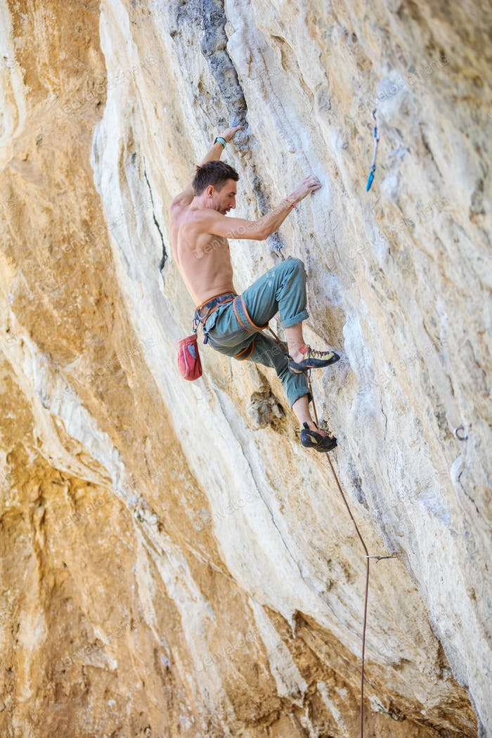 Rock climber on challenging route on cliff